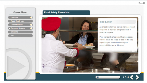 A screenshot from the food safety E-Learning (online) course, showing food being served to a customer by a chef, in a commercial kitchen.